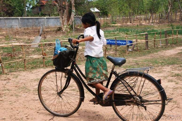 Small Cambodian girl on bicycle too big for her